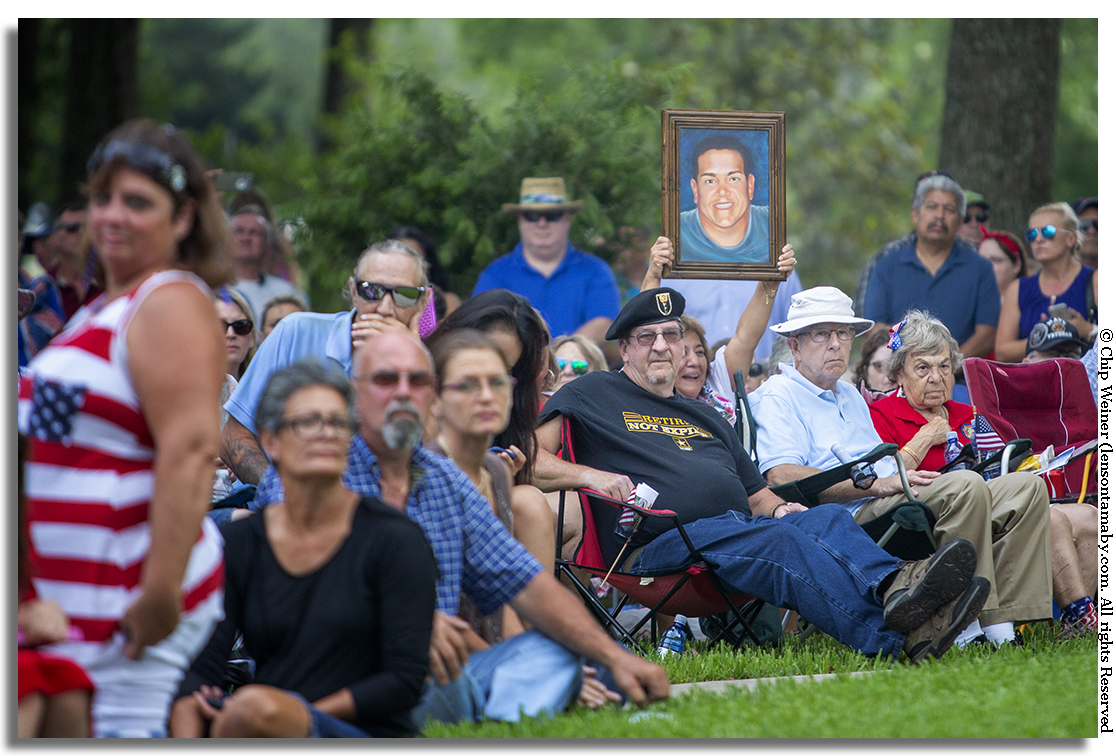 A proud mom holds up painting of her son while The Hernando High School Royale Regiment plays the Army march