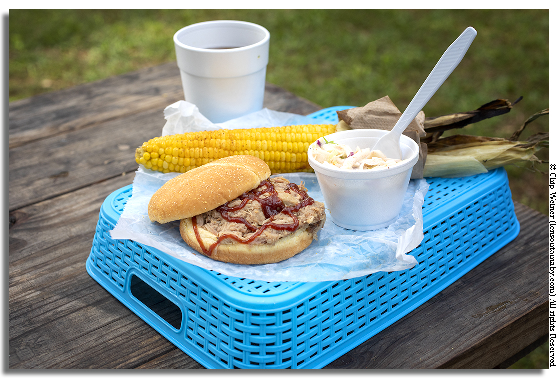 A BBQ pulled pork sandwich, coleslaw, and a fresh ear of grilled and buttered corn on the cob along with some sweet tea