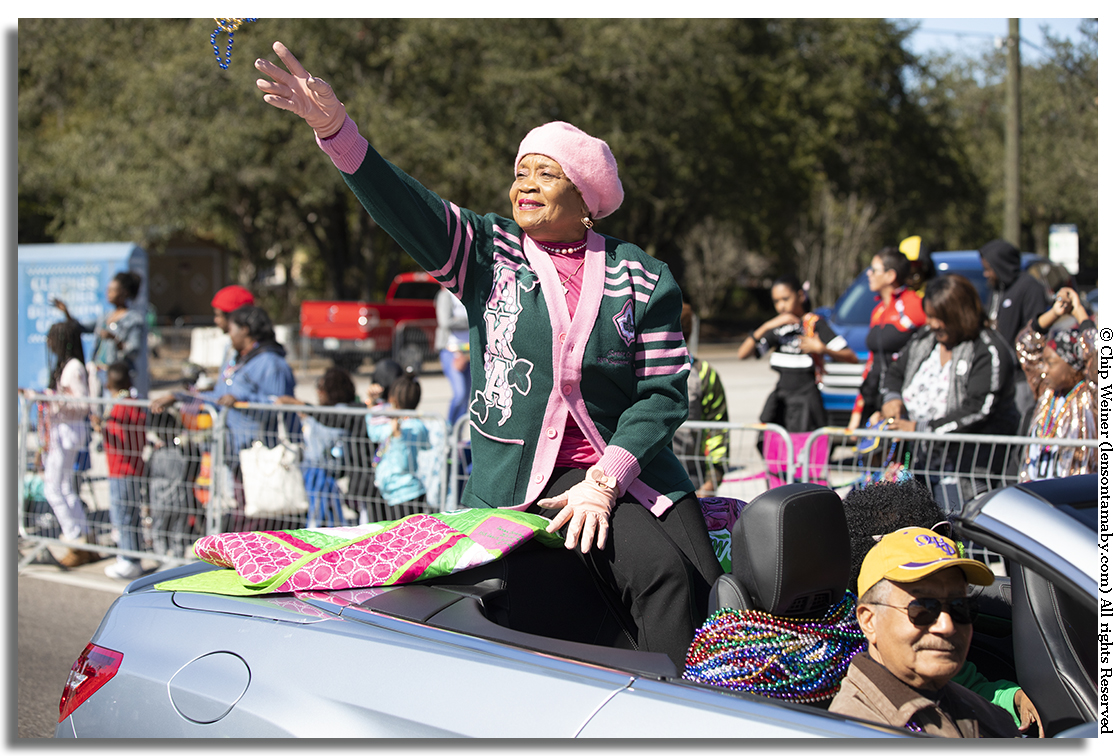 Parade Grand Marshall Carolyn Hose Stewart tosses beads while being cheered on