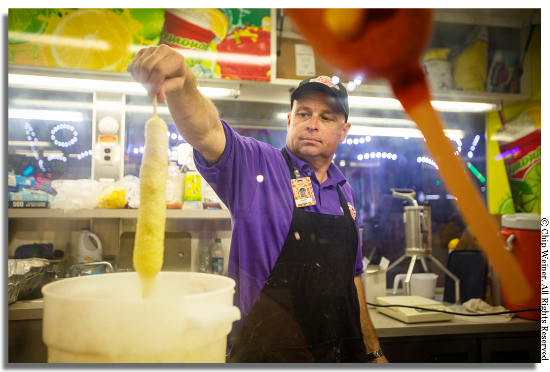 Speaking of corn dogs, what's a fair without a foot-long? Jason Zokka with Potopas Concessions dips a 12 incher in batter before dropping it into the deep fryer. Yes, I did as a matter of fact… with a little mustard.