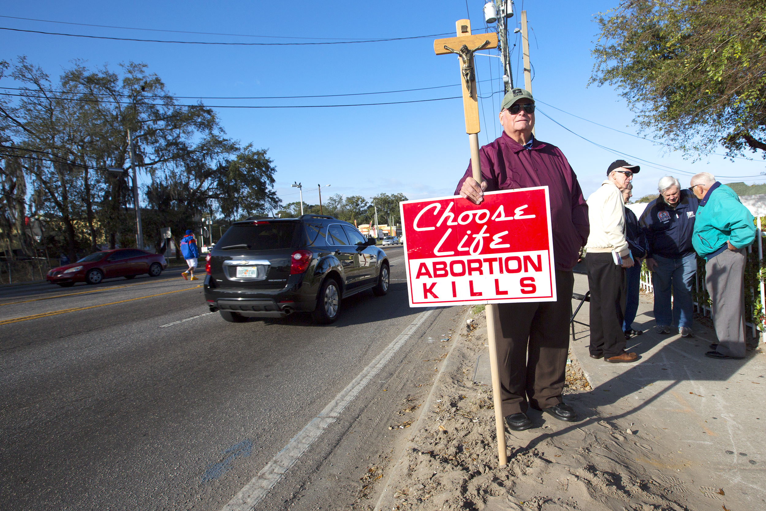 Jim Haskins holds a crucifix with a choose life sign attached on Fletcher ave with other demonstrators in the background 2.jpg