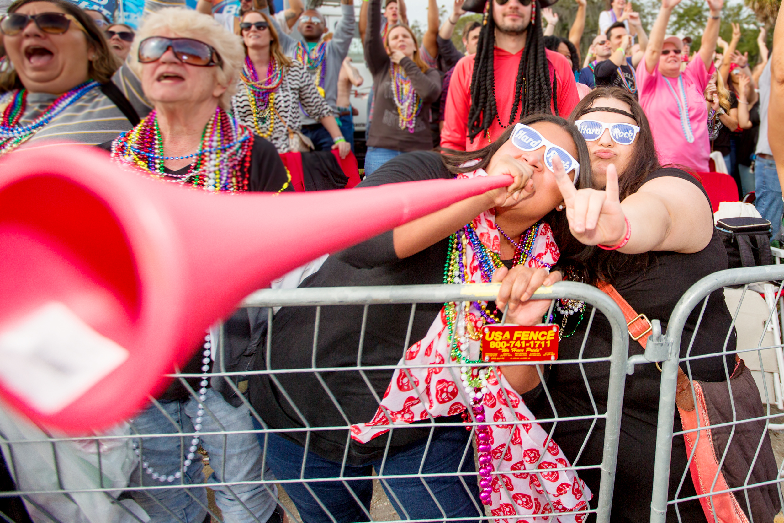 Angelica Mondragon toots her horn for beads while her friend Alexandra Wright rocks on.jpg