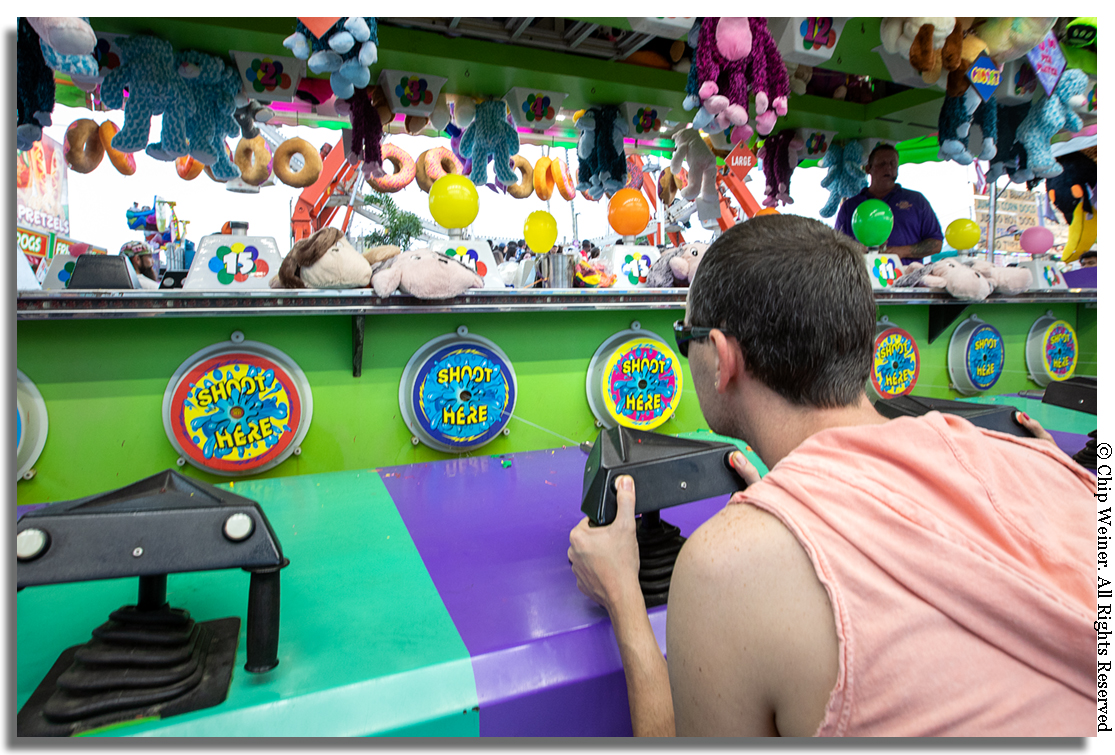 """ Want a prize? Pick your size! Winner every time "" says the raspy voice over the PA system at this game where players shoot water at a target which inflates a balloon. The first balloon to pop wins!"