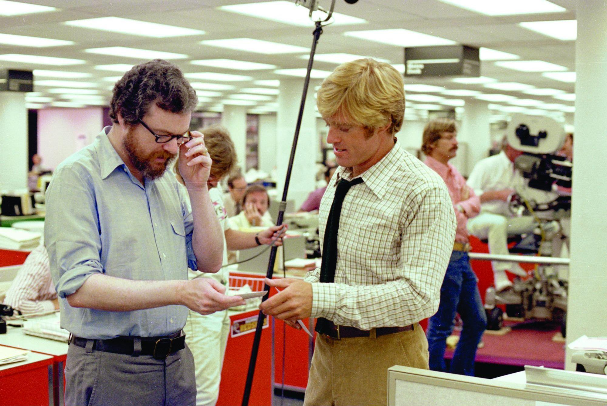 Pakula and Redford discuss a scene on the Washington Post newsroom set.