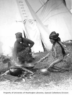 two native american women cooking over a fire in front of a teepee, 1929-1932 ~