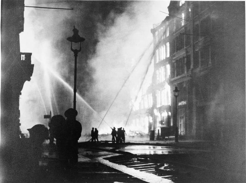 Members of the London Fire Brigade train their hoses on burning buildings in Queen Victoria Street, EC4, after the last and heaviest major raid mounted on the capital during the 'Blitz'. For six hours on the night of 10-11 May 1941, aircraft of the Luftwaffe dropped over 1,000 tons of ...   Sourced & Licensed from © IWM Imperial War Museum Non Commercial Licence
