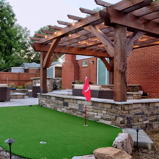 A bonus pic, because it's Halloween 🎃, and we know you wanna see more putting green! ⛳ . . This outdoor living space includes a multi-level patio with seatwalls, grill bar, pergola, seating area and firepit. Designed by Josh Smith, a talented landscape designer, and our most recent hire. Installed by the @outdoorartisan team. Photo by @brucesaundersphotography. . . . #brucesaundersphotography #outdoorartisan #techobloc #patios #patio #backyardgoals #outdoorspaces #outdoorroom #pergola #pergolas #cedar #backyarddesign #backyardideas #backyards #firepit #firepits #stonewall #seatwall #grillbar #outdoorlivingspace #outdoorspace #outdoordecor #backyardliving #outdoorentertaining #patiodesign #paverpatio #pavers #patiolife #puttinggreen #puttinggreens