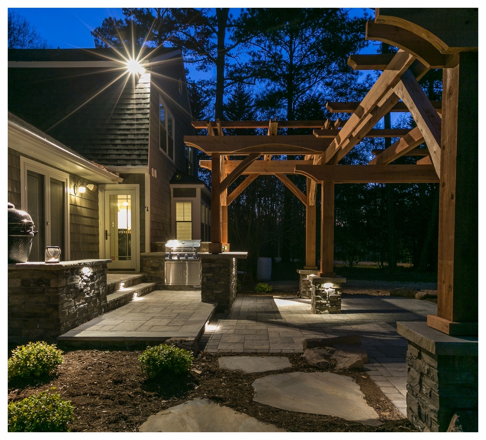 A multi-level outdoor kitchen area with custom pergolas covering the dining bar and seating area. All designed and built by the Outdoor Artisan team.