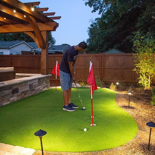 So thrilled that our client was willing to pose for an action shot on his new putting green! You can see here how much the landscape lighting helps illuminate everything so he can practice his game into the night. Plus, just looks cool, 😎 even when the wide angle camera lens makes the lights appear crooked. . . . . #brucesaundersphotography #outdoorartisan #puttinggreen #puttinggreens #putting #pergolas #pergola #puttingpractice #backyardgoals #backyardputtinggreen #charlottedesign #backyarddesign #backyardideas #backyards #outdoorlivingspace #outdoordesign #backyardfun #golflove #backyardgolf #outdoorentertaining #outdoorspaces #outdoorlivingspace #landscapelighting #outdoorlighting #golflove #charlottehomes #landscapers #putter