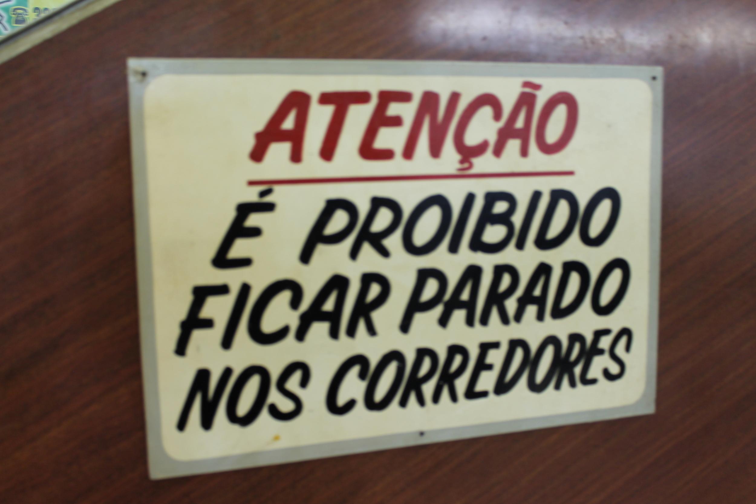 Essa placa fica na Galeria do Presidente (conhecida como Galeria do Reggae) em São Paulo. O lugar que tem lojas e restaurantes, aberto como espaço público proíbe as pessoas de ficarem paradas no corredor. Como é que é possível olhar as vitrines, então? E como um espaço público pode ser proibido a circulação?
