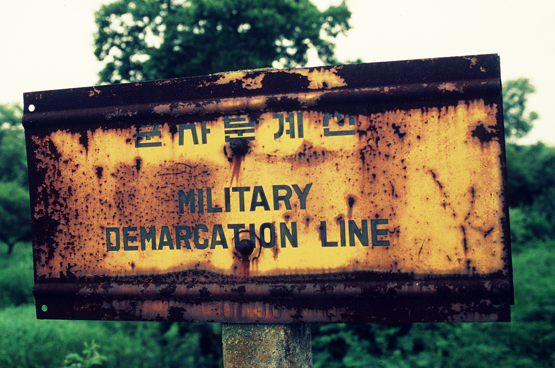 Photo_of_the_Military_Demarcation_Line_(MDL),_sign_located_in_the_woods_at_Pan_Mun_Jom_(DMZ),_separating_North_and_South_Korea_F-3203-SPT-94-000314-XX-0085.jpg