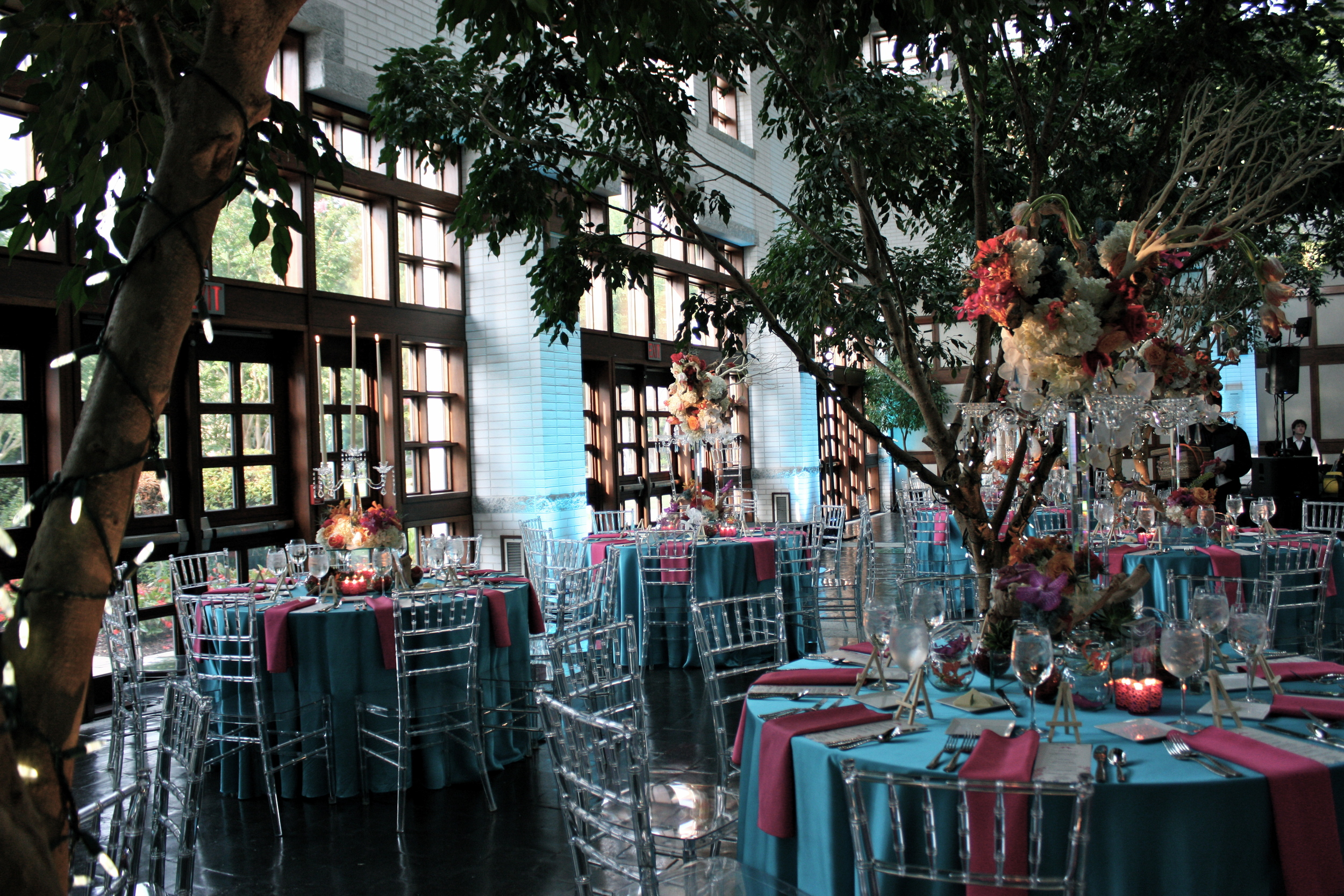 The reception was held in MOCA's main hall, with colors focusing on the couple's choice of an underwater theme. The hall has four trees installed through the ground, adding an organic touch and a unique look to the interior.   The candelabra was then mounted on a glass square base containing a sand-based terrarium of succulents. Surrounding the table were glass orbs of red moss, small fishbowl glasses of gloriosa lilies, and cut vanda orchid blooms.   Congratulations to Nina and Adam! A beautiful wedding for a beautiful couple.