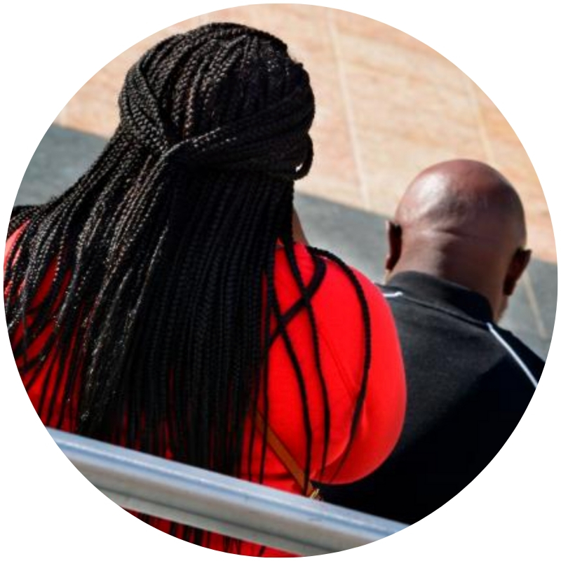 Image description: Two Black people, seen from behind. One is wearing red and their hair is styled in long braids. The other is bald and wearing black. (Credit: Robert Alexander/Getty via CNN)
