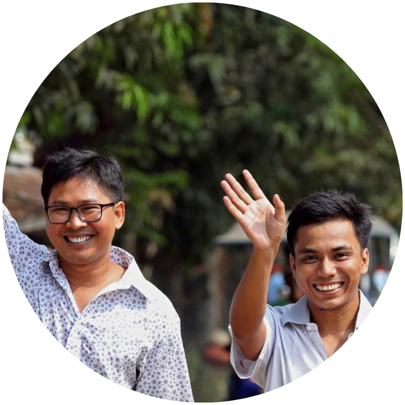 Image description: Reporters Wa Lone and Kaw Soe Oo, wearing light collared shirts and smiling, seen from the chest up. (Credit: Ann Wang/Reuters)