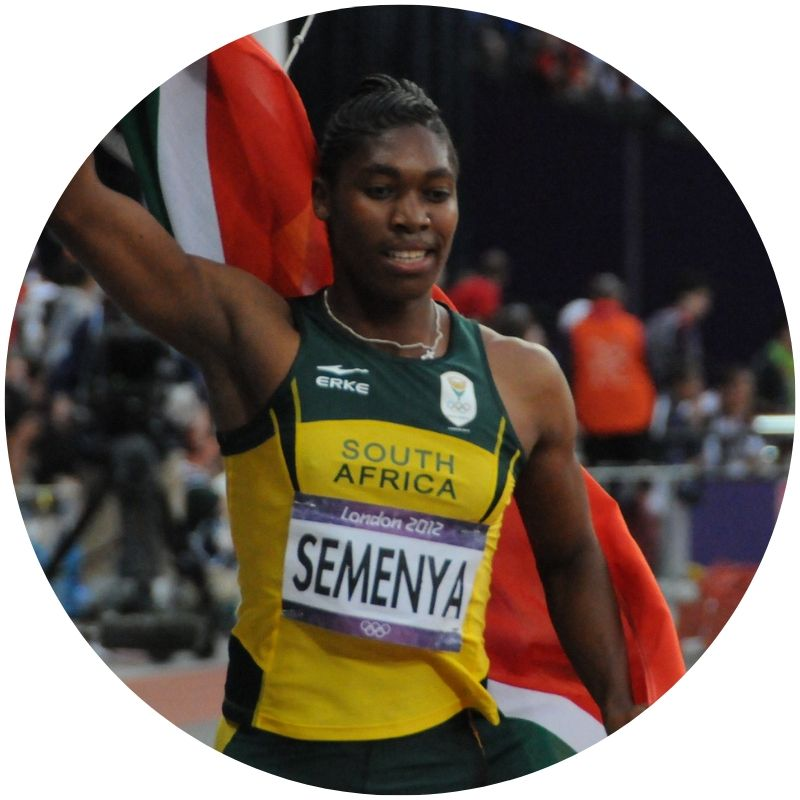 Image description: Caster Semenya seen from the waist up in a green and yellow jersey. She has one arm raised and is holding a South African flag behind her. (Credit: Citizen59 via  Flickr )
