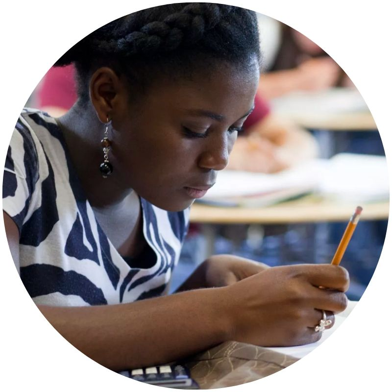 Image description: A Black student in a black and white top sits with pencil in hand, atop a textbook (Credit: Weston Colton/Getty Images/Rubberball)