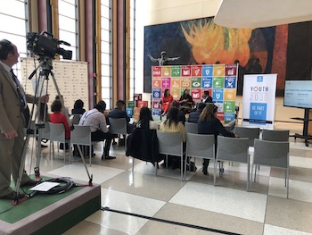 [Image Description: small meeting room, pictured from the back right corner. Three people sit facing the audience in front of a large banner of the Sustainable Development Goals.]