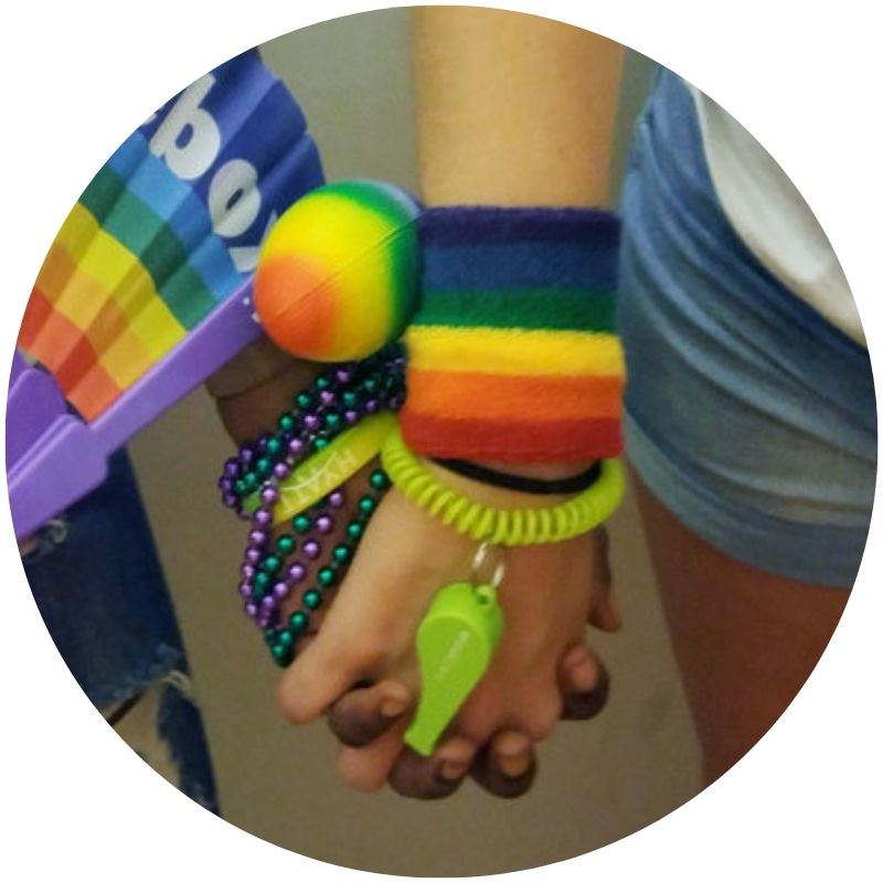 Image description: Two people holding hands, zoomed to show the hands and wrists only. One person has lighter skin, the other darker, and both are wearing colorful bracelets. (Credit: UN News/Elizabeth Scaffidi)