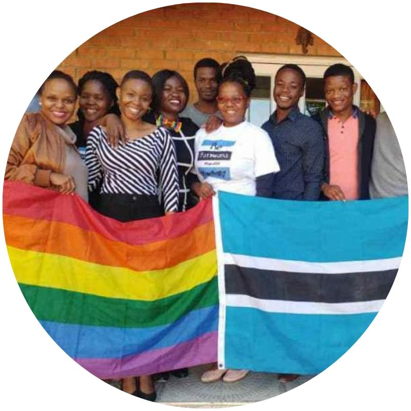 Image description: Group of young people. Half of the group holds up a rainbow flag, the other half holds a flag of Botswana, which has five horizontal stripes: blue, white, black, white, blue (Credit: Caine Youngman)