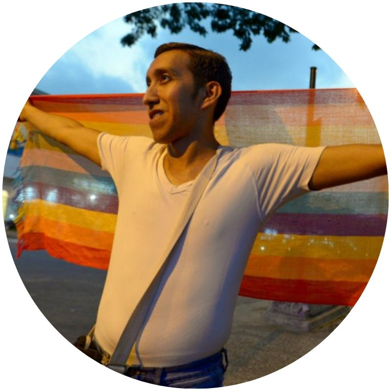 Image description: A person with short hair and light skin, wearing a white t-shirt, with arms outstretch. They are holding a stretched scarf with rainbow stripes behind themselves (Credit: Marcos Pin, AFP via  France24 )