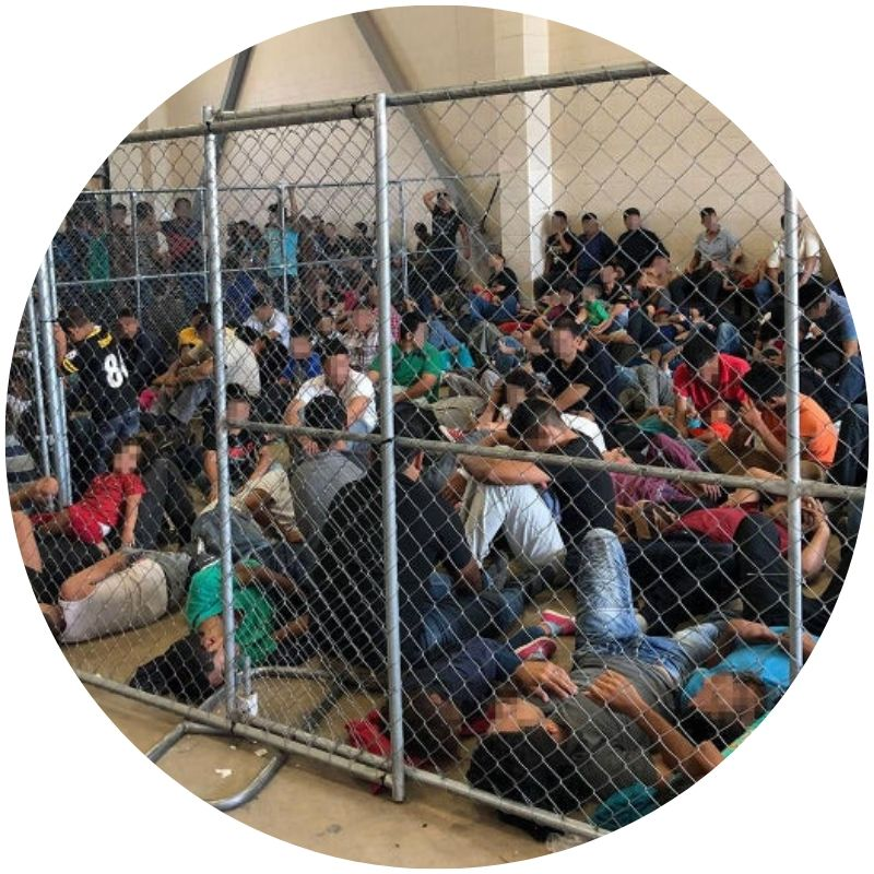 Large group of people sitting on a concrete floor behind a chain-link fence. The floor is barely visible due to the large number of people being held (Credit: Office of Inspector General/Department of Homeland Security via Getty Images)