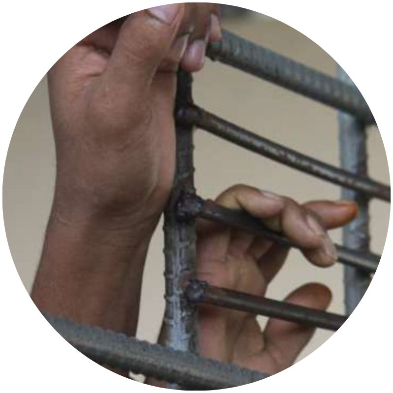 Two brown hands grasping horizontal bars on a gate (Credit: UNHCR/V. Tan)