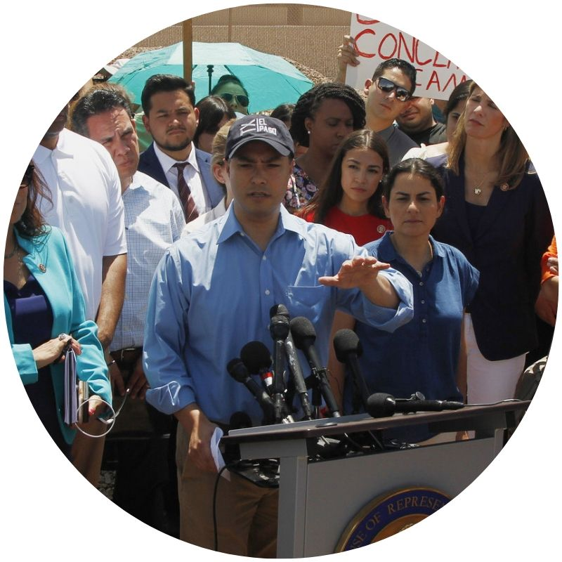 Rep. Joaquin Castro (D-Texas) speaks at a podium after touring the Border Patrol station on July 1. A crowd of people can be seen behind him. (Credit: Cedar Attanasio/AP)