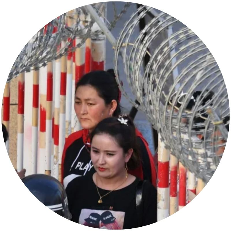 Two women with hair pulled back and wearing black enter a bazaar in China's Xinjiang region. Barbed wire is visible at the top of the photo. (Credit: Greg Baker / AFP / Getty Images)