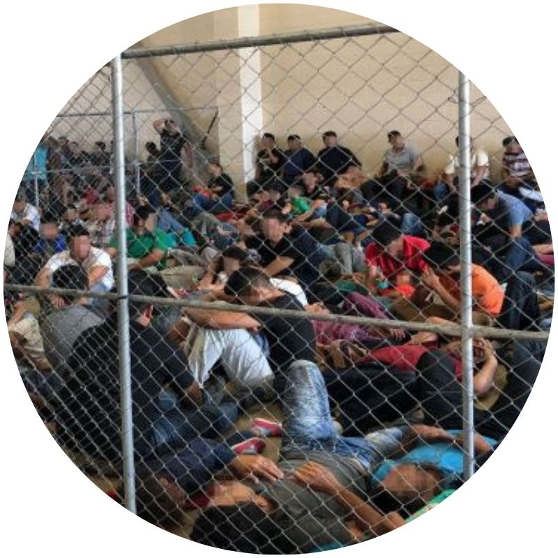 A group of migrants, including small children, is seen behind a chain link fence. Most are sitting on the ground. (Credit: Office of Inspector General/Department of Homeland Security)