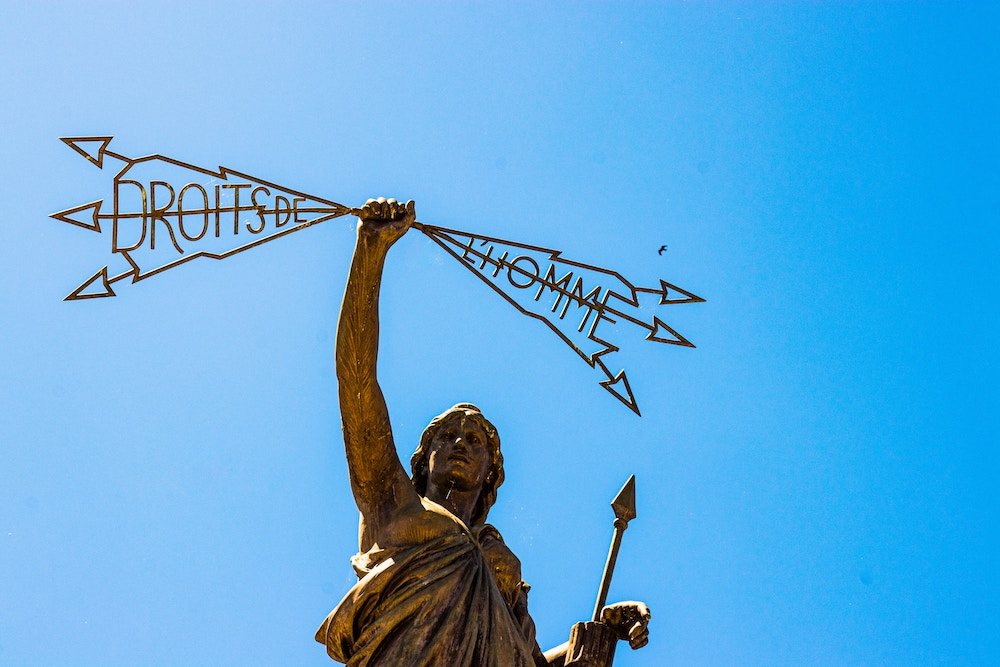 """Statue of man holding banner that says """"droits de l'homme"""" - """"human rights"""" in French (Image by DDP via  Unsplash )"""