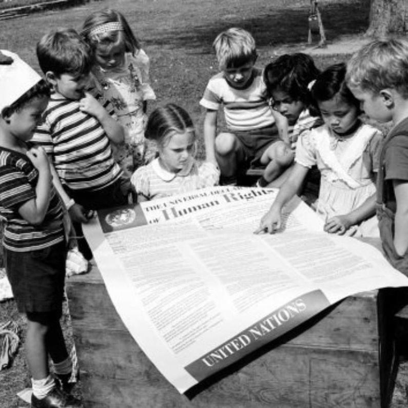 CHILDREN EXAMINING THE UDHR (VIA  UN PHOTO )