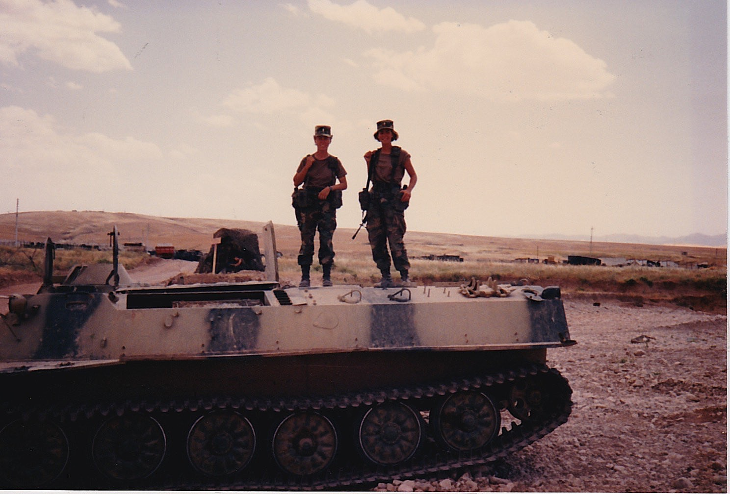 Kokolis and a friend atop a blown out tank in Iraq