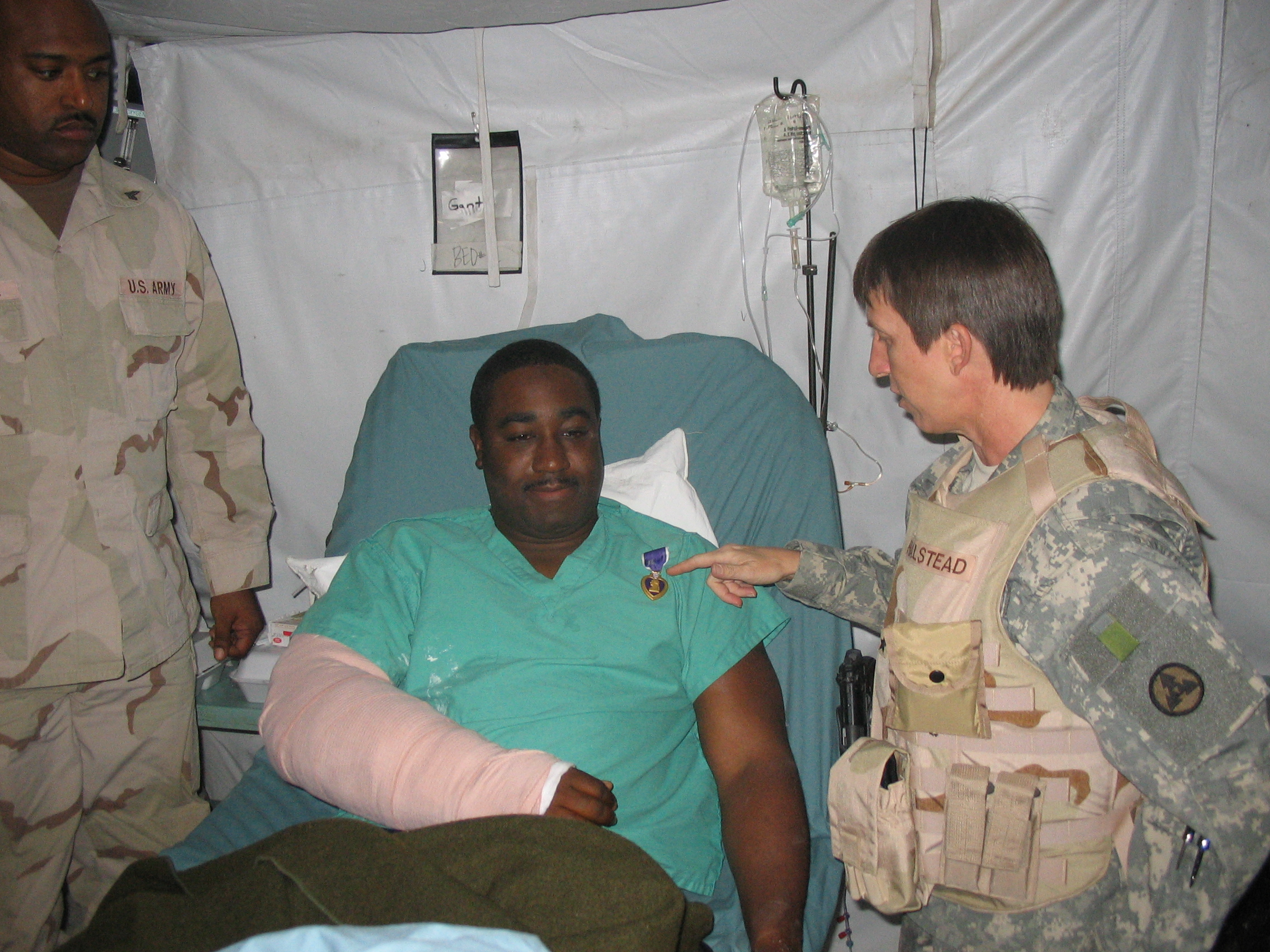 Brigadier General Halstead visits a wounded soldier to pin on his purple heart.