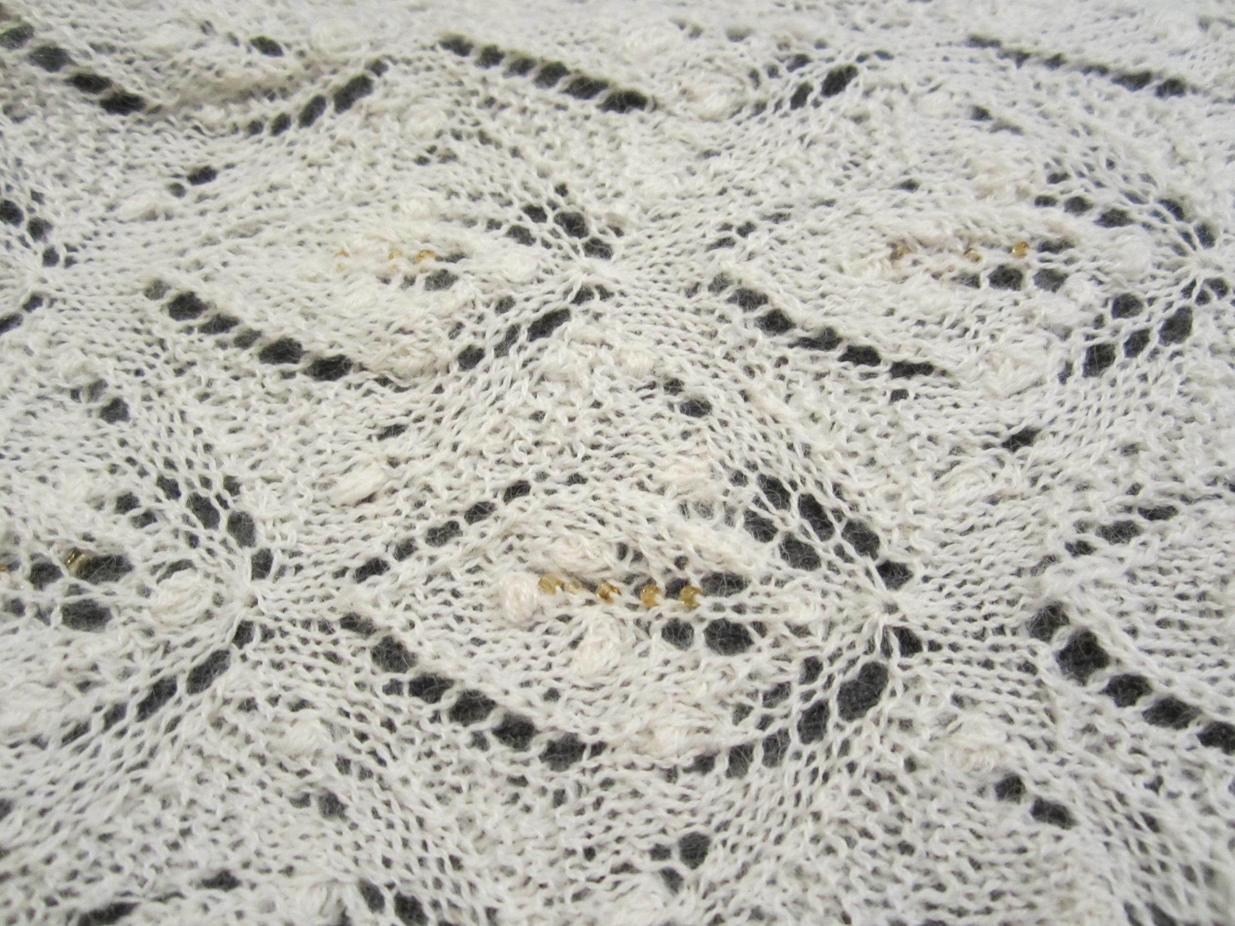 Traditional Estonian lace shawl pattern updated to incorporate gold glass beads down the center of each leaf motif.