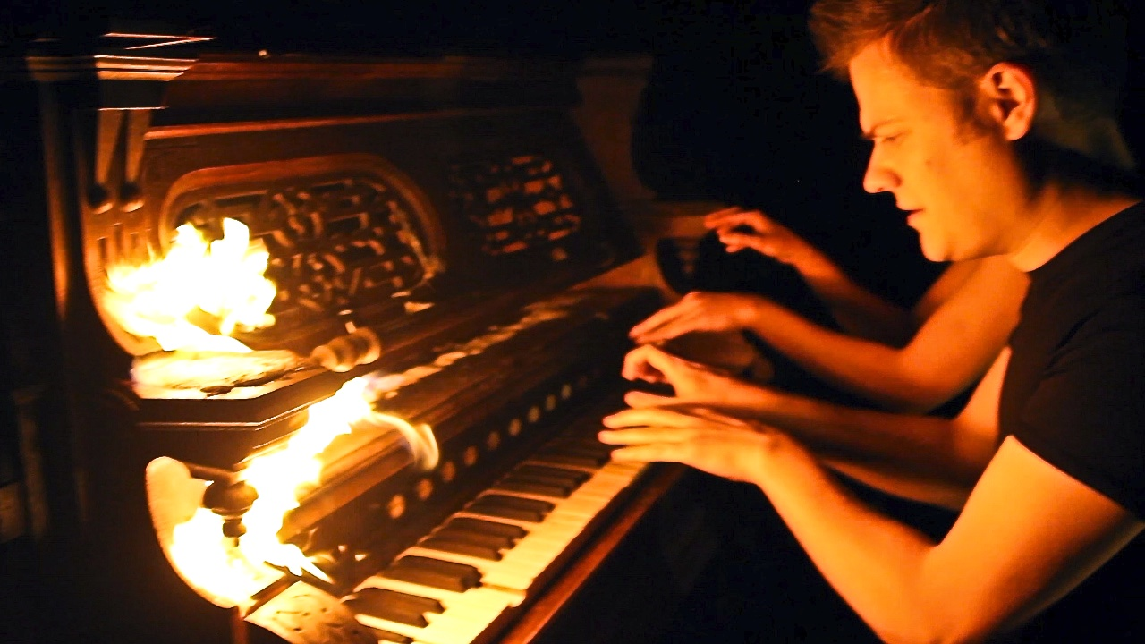 Anderson and Roe playing piano with fire.jpg