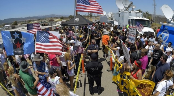 Protesters from opposing sides demonstrate outside a US Border Patrol station in California on 4 July 2014.