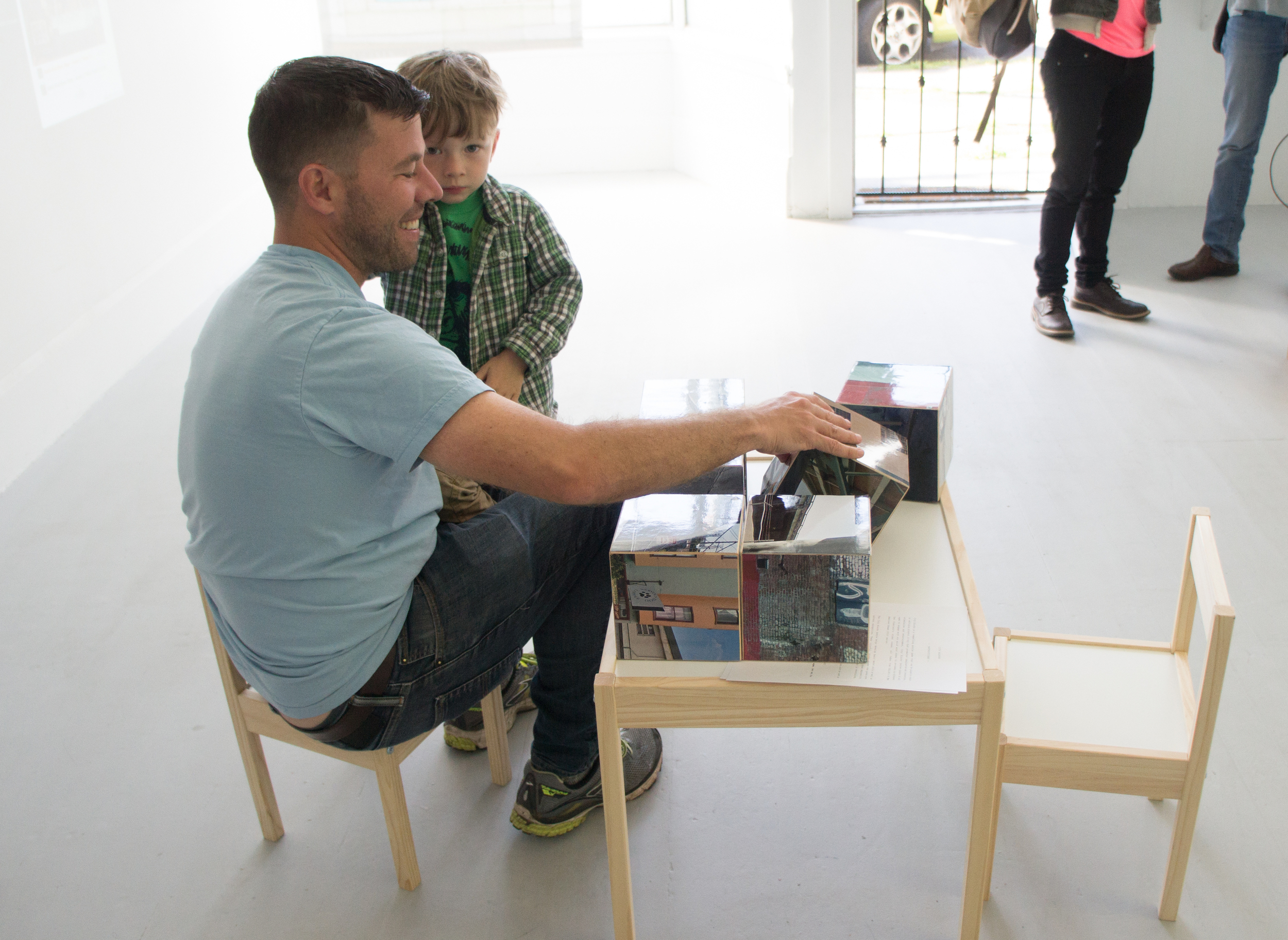 COLL.EO's City Blocks,six wooden blocks with images measuring 6 x 6 x 6 inches, arranged on an IKEA's LÄTT children wooden table and two wooden chairs. Table size: 24 ¾ (L) x 18 ⅞ (W) x 17 ¾ (H). Chair size: 11 (L) x 11 (D) x 11 (H).