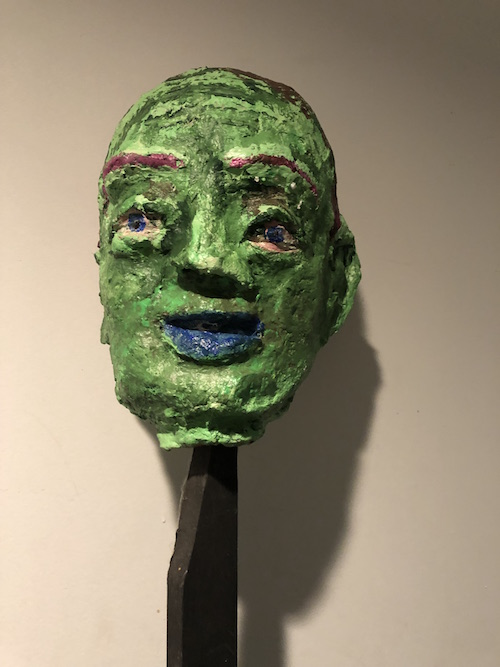 """#21 Matt Freedman  Green Head on a Pike  Paper, acrylic paint, wood 7 x 6 x 10 in. With wooden pike total height is 79"""", 2017"""