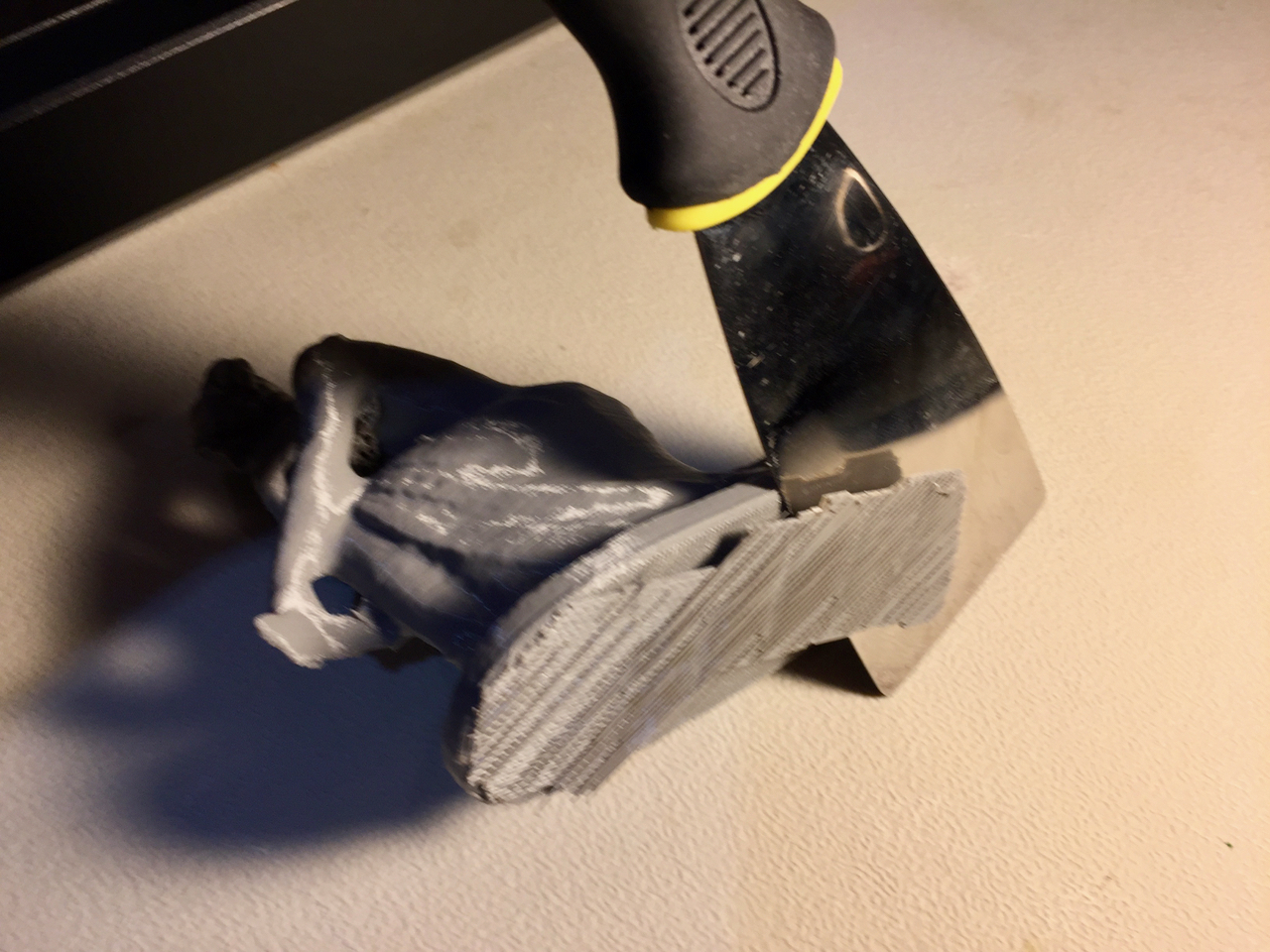 Prying off a raft from a print made on the MakerBot Replicator+