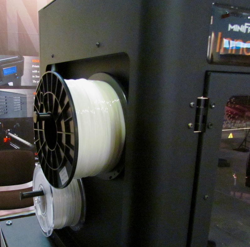 Filament spools are mounted on the exterior of the Minifactory desktop 3D printer