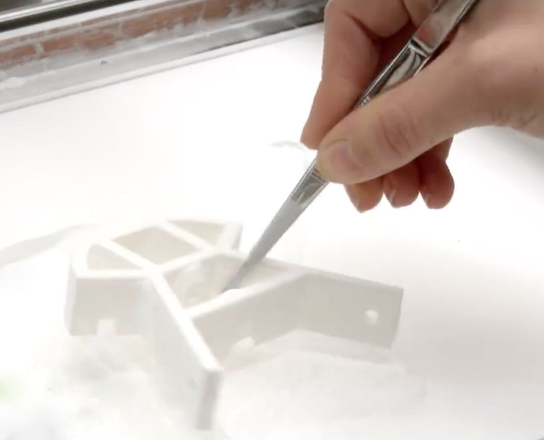Removing a completed SLS 3D print from the powder bed