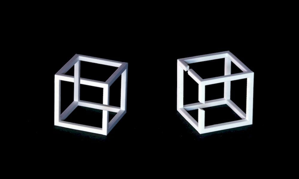 """A 3D printed """"Impossible Cube"""" at left - but seen at a different angle at right"""