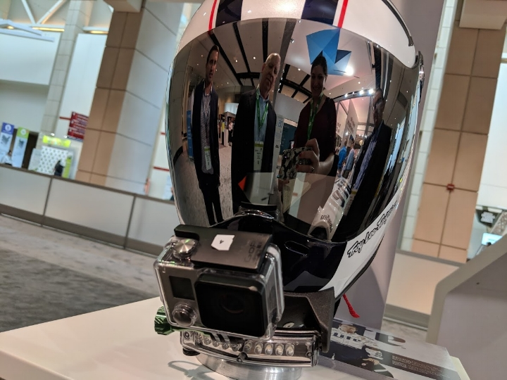 Reflected in the helmet, Rich Garrity, President, Americas (left) and Pat Carey, SVP, Sales (middle) show me (right) a custom-made GoPro mount 3D printed for Team Penske as an example of customized device holding capabilities with carbon fiber materials