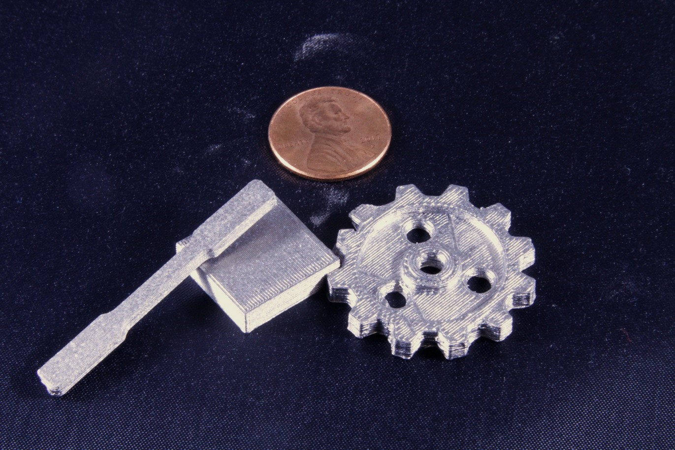 3D printed titanium gear, dogbone, and block [Image: nScrypt]