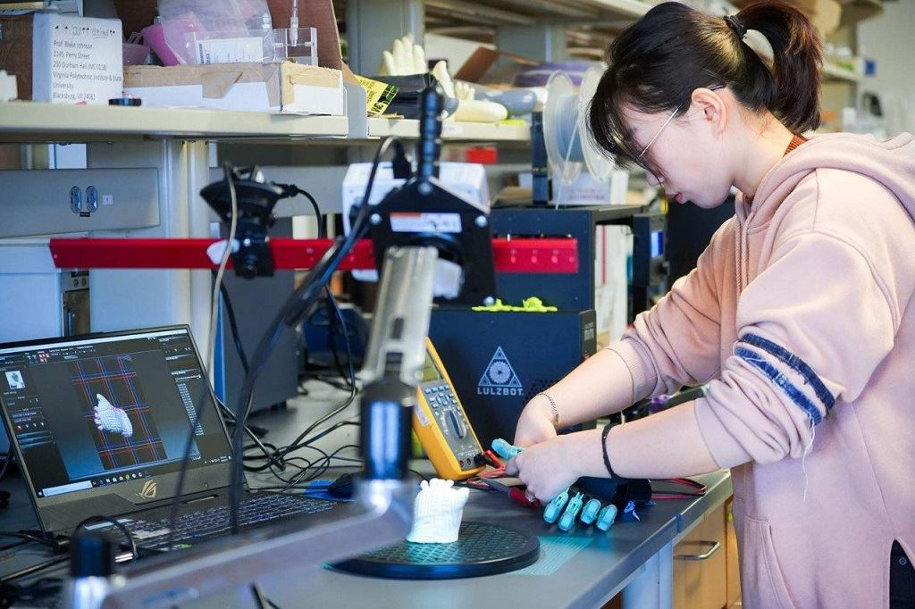 Yuxin Tong, an industrial and systems engineering graduate student, adjusts a 3D printed prosthetic. Tong was first author of a newly published research study about integrating electronic sensors in personalized 3D printed prosthetics. [Image: Linda Hazelwood/Virginia Tech]