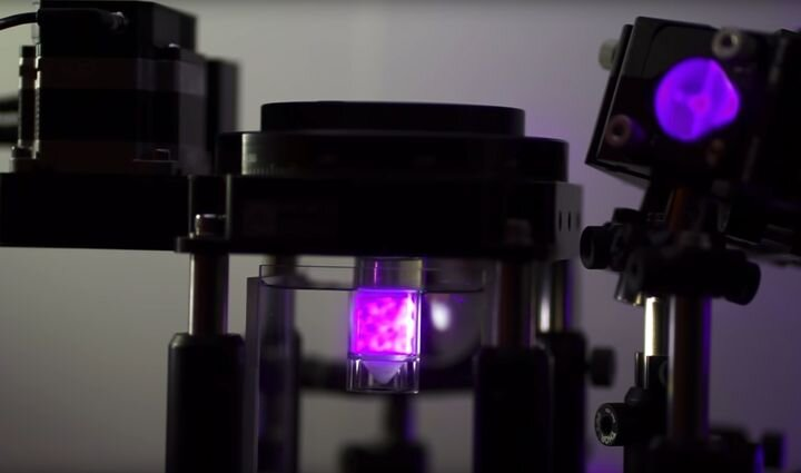 View of Readily3D's volumetric 3D printer, with illuminated build chamber in the center [Source: Readily3D]