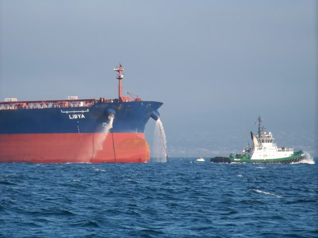 Super tanker bow and a tug boat