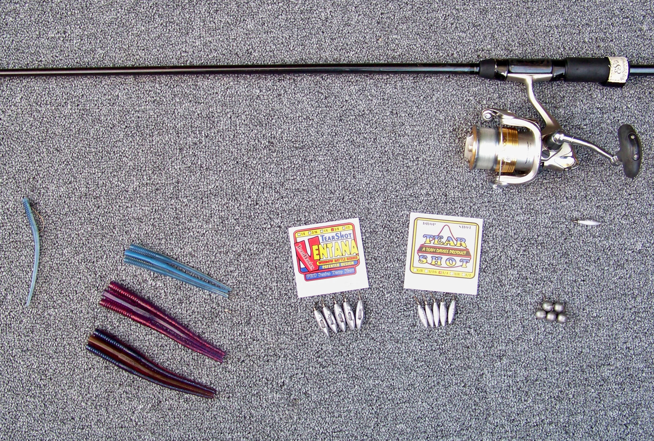 "With clouds and strong wind present, the fish favored Trigger X 5.5"" Probe Worm Cheap Shot color (middle position) & Dirty Grape color (bottom position). When sunshine, blue skies and a calm breeze  appeared, the 4"" Probe Worm Pro Blue color (top position) scored.  The 3/8 oz. Ventana rattling drop shot weight (left position), 1/4 oz. Tear Shot Slim Shot (center position), the 3/8 oz. Tear Shot Bulk Shot tungsten weight (right position). The length of the drop is shown from the individual Slim Shot weight below the reel and the single Pro Blue worm far left, The 8 lb. fluorocarbon line is not visible in the photo."