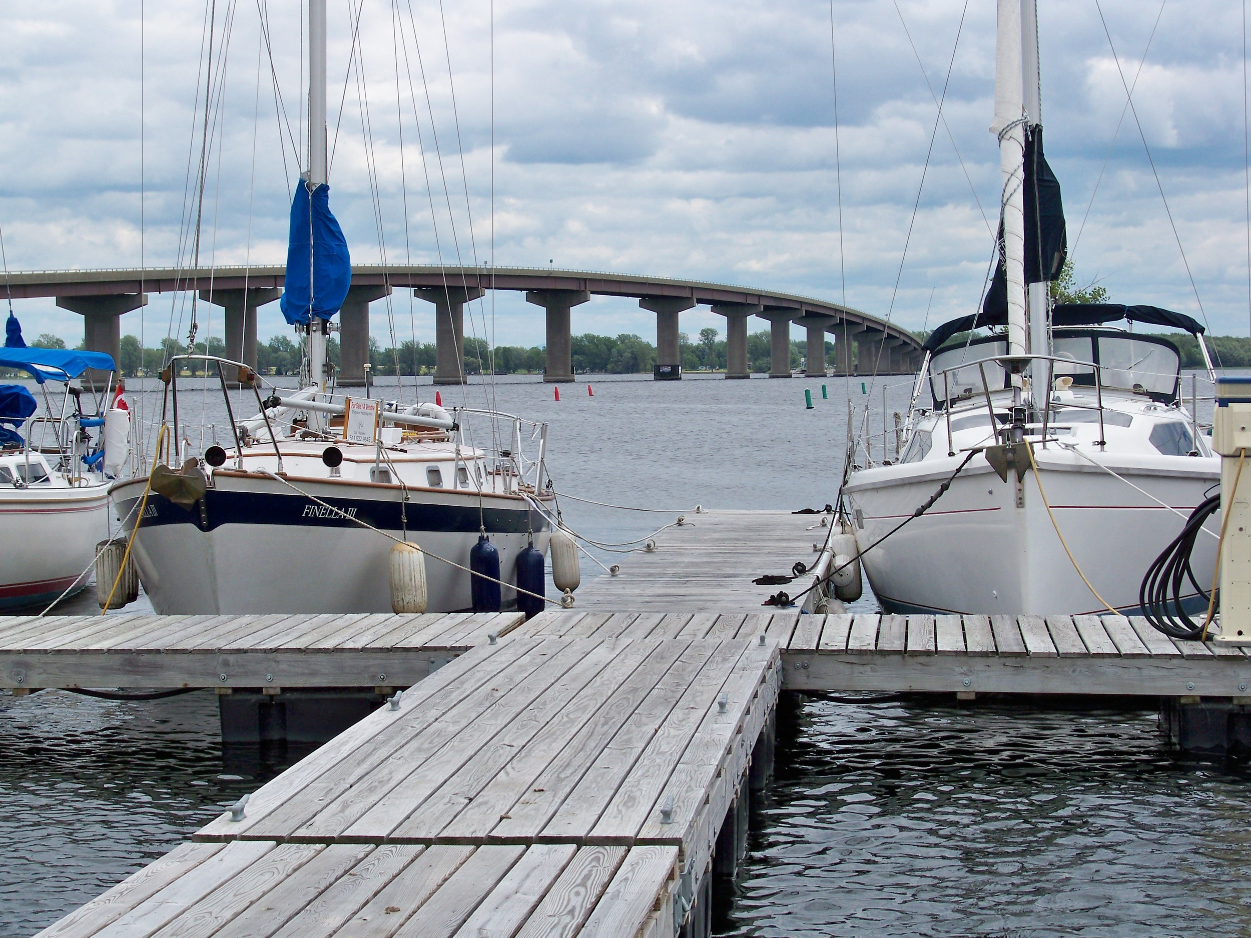 Marina docks at Rouses Point New York in the foreground and bridge pilings with current in the background add this to a Milk Run.