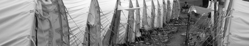 Traumatically displaced people in Leogane, Haiti are sheltered in tents set close together in rows.
